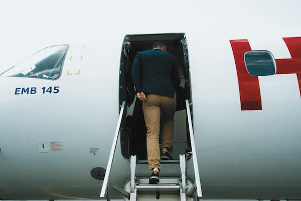 A picture of a man getting onto a plane, which represents a new hire employee being onboarded into a new organization